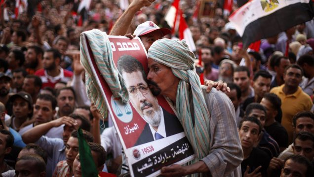 Supporter of Muslim Brotherhood's presidential candidate Mohamed Morsy kisses his picture during a celebration of his victory at the election at Tahrir Square in Cairo